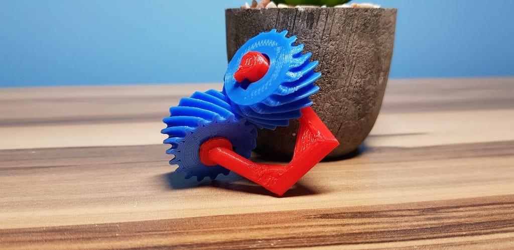 Zwei blaue 3D-Gedruckte Zahnräder sind zu 90 Grad versetzt und mit rotem Halter verbunden.